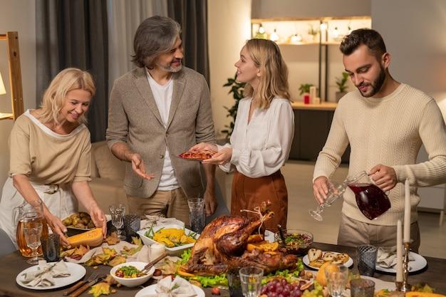 집에서 만든 파이, 구운 옥수수, 샐러드 및 기타 음식을 저녁 식사 전에 추수 감사절 테이블에 올려놓는 행복한 젊고 성숙한 가족