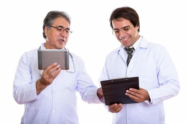 Счастливый молодой и старший персидский мужчина-врач улыбается и держит цифровой планшет и буфер обмена