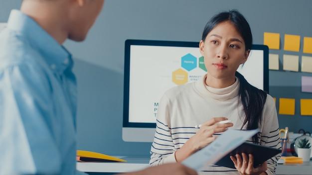 Счастливые молодые азиатские бизнесмены и деловая женщина встречаются, обсуждая новые идеи о проекте