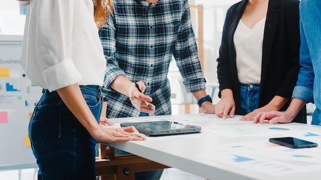 幸せな若いアジアビジネスマンやビジネスウーマン会議成功戦略を計画して一緒に働いている新しい書類プロジェクトの同僚についてブレーンストーミングのアイデアを会議は小さなモダンなオフィスでチームワークをお楽しみください。