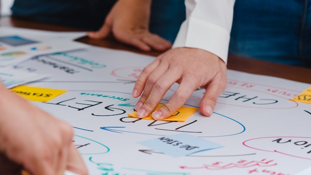 Счастливые молодые азиатские бизнесмены и деловые женщины встречают мозговой штурм по поводу нового проекта по оформлению документов