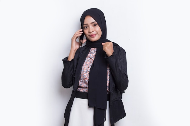 Счастливая молодая азиатская красивая мусульманская женщина с помощью мобильного телефона, изолированного на белом фоне