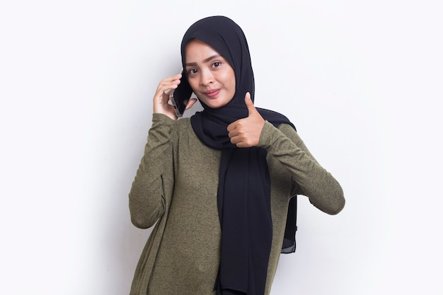 Happy young asian beautiful muslim woman using mobile phone isolated on white background