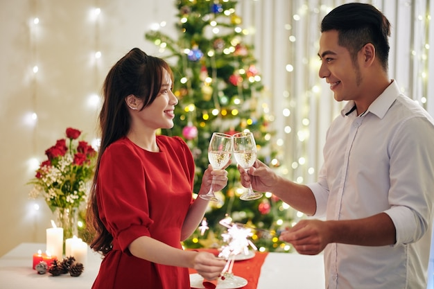 家でクリスマスを祝うときにシャンパンを飲み、ベンガルライトを燃やす幸せな若いアジアのボーイフレンドとガールフレンド