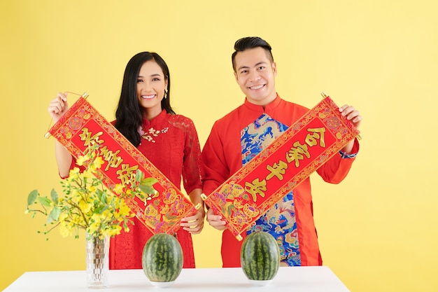 Happy young asian boyfriend and girlfriend in traditional dresses showing wall decorations for lunar new year with best wishes inscription standing at dinner table