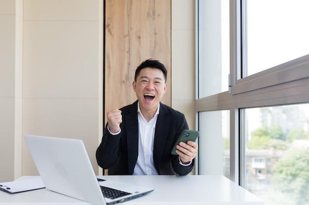 勝者の感情とカメラを見てオフィスで幸せな若いアジアのビジネスマン