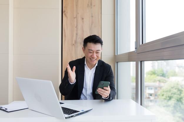 사무실에서 휴대전화를 보고 있는 행복한 젊은 아시아 사업가