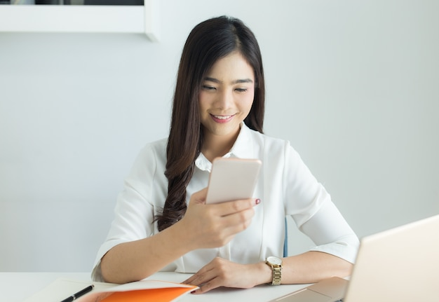 Happy young asian business woman use smartphone for working at her workplace.