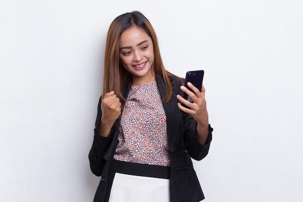 Счастливая молодая азиатская бизнес-леди с помощью мобильного телефона, изолированного на белом фоне