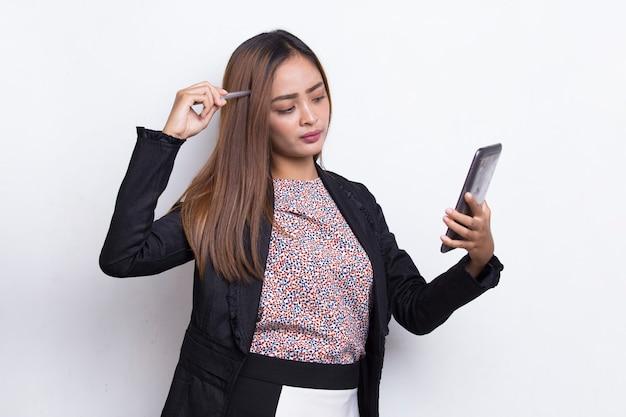 白い背景で隔離の携帯電話を使用して幸せな若いアジアのビジネス女性