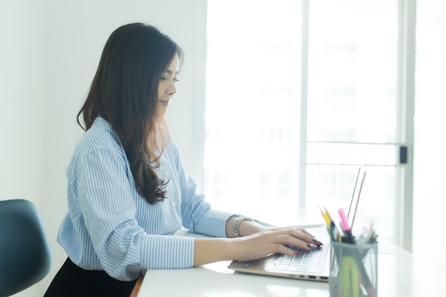 Happy young asian business woman working on her laptop at workplace.