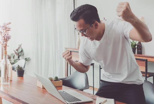 ラップトップでホームオフィスで働く幸せな若いアジア人のビジネスマン