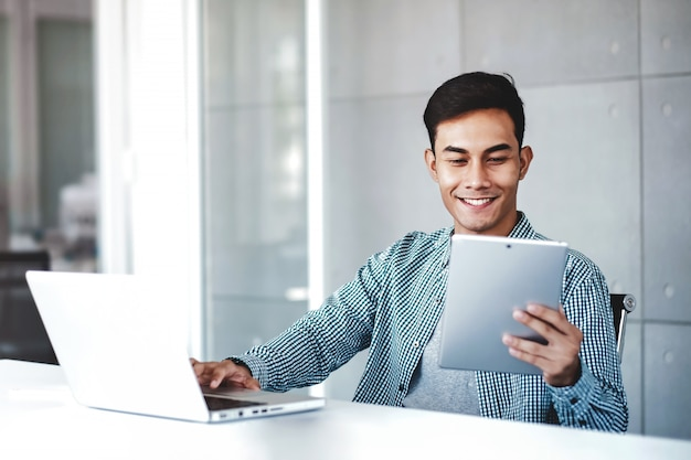 Happy young asian businessman working on computer laptop in his workplace