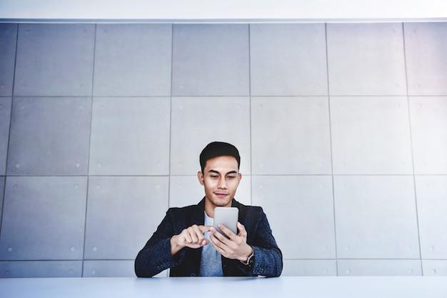 スマートフォンに取り組んで幸せな若いアジア系のビジネスマン。