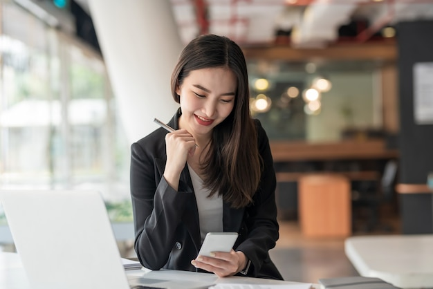 Счастливый молодой азиатский бизнесмен, держащий ручку с помощью смартфона в современном офисе.