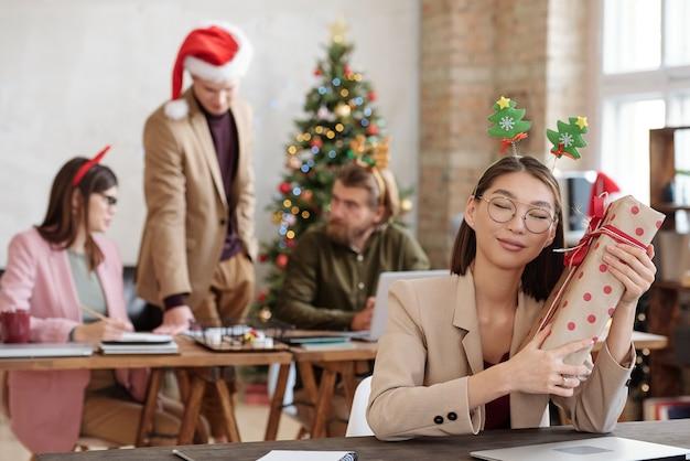 크리스마스 머리띠를 한 행복한 젊은 아시아 여성 사업가가 테이블 옆에 앉아 눈을 감고 있는 동안 큰 포장된 선물 상자를 귀 옆에 들고 있습니다.