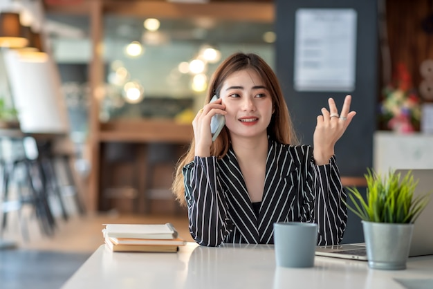 Счастливая молодая азиатская коммерсантка работая на компьтер-книжке и говоря на смартфоне