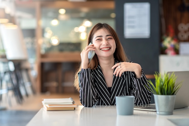 Счастливая молодая азиатская коммерсантка работая на компьтер-книжке и говоря на smartphone.