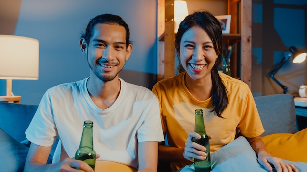 Happy young asian couple enjoy night party event sit couch in video call with friends
