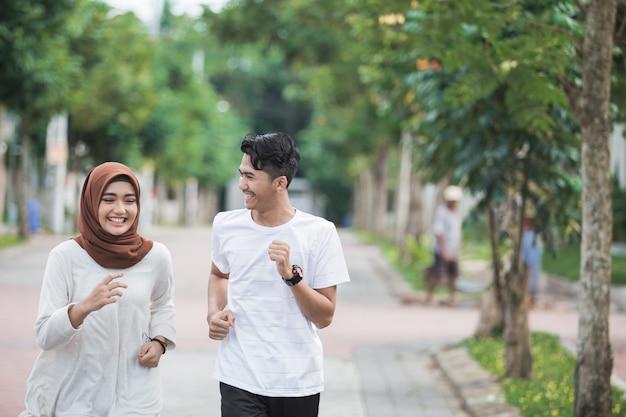 幸せな若いアジアカップル運動とウォームアップ