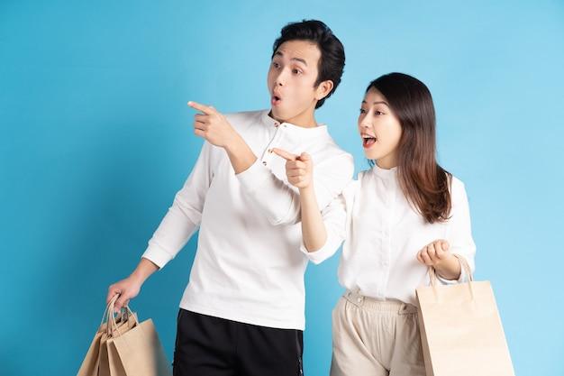 幸せな若いアジアのカップルが楽しく買い物に行く