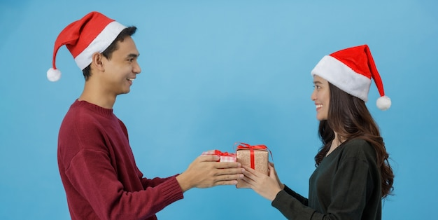Happy young asian couple holding christmas gift boxes with happy smiling face isolated on blue background in studio shot.christmas celebration of lover concept.