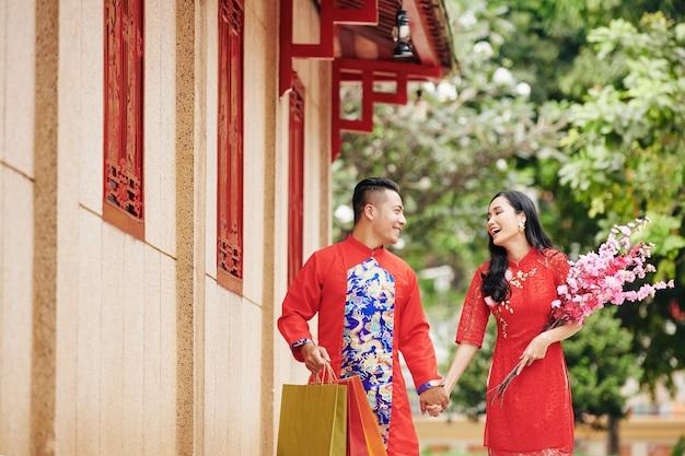 Счастливая молодая азиатская пара, держась за руки, гуляя на открытом воздухе в традиционной одежде с цветущими ветвями и сумками для покупок