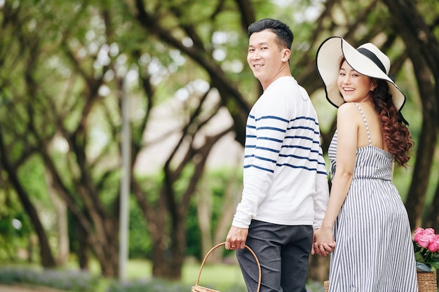 Happy young asian couple holding hands when walking in park and turning back to camera