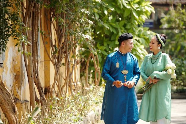전통적인 드레스와 머리 조각을 입은 행복한 젊은 아시아 커플은 여름날 야외에서 걸을 때 웃고 이야기합니다