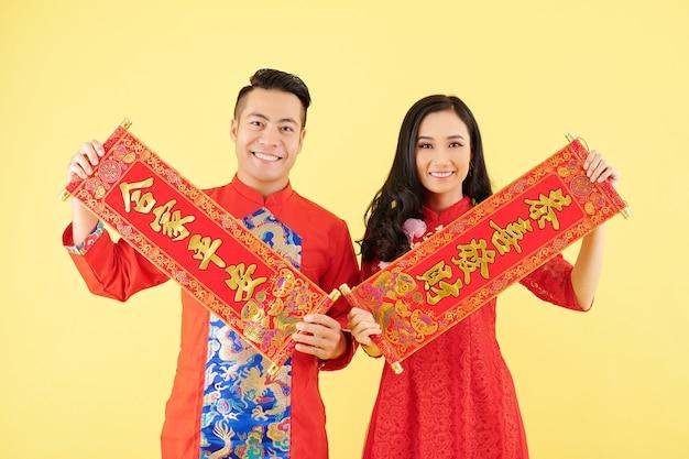 来年の碑文に最高の願いを込めて二行連句を示す伝統的なドレスを着た幸せな若いアジアのカップル