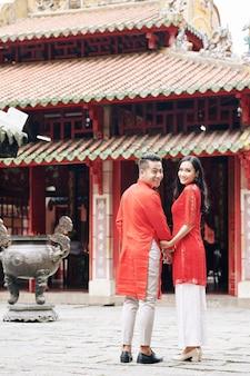仏教寺院に歩いて、振り返って、カメラに笑顔の伝統的なドレスを着た幸せな若いアジアのカップル