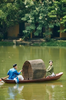 베트남 전통 드레스를 입은 행복한 젊은 아시아 커플이 호수에서 작은 보트를 노를 저어