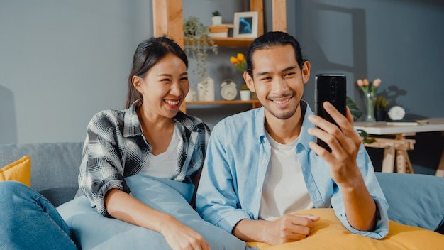 Happy young asian couple man and woman sit couch use smartphone facetime video call with friends and family