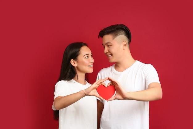 Счастливая молодая азиатская пара с бумажным сердцем