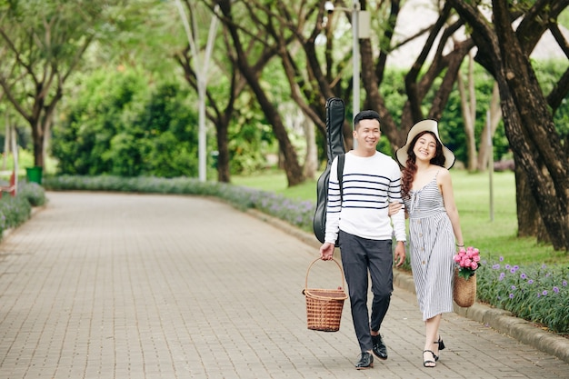 Happy young asian couple with picnic baskets and guitar walking in city park