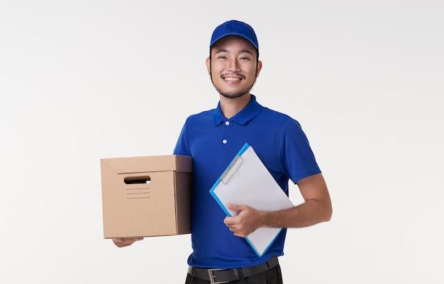 白い背景で隔離クリップボードとボックスを保持している幸せな若いアジアの配達人。