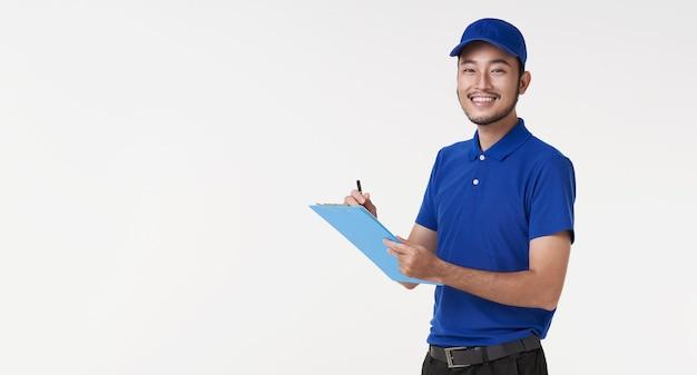 白い背景で隔離クリップボードを保持している幸せな若いアジアの配達人。