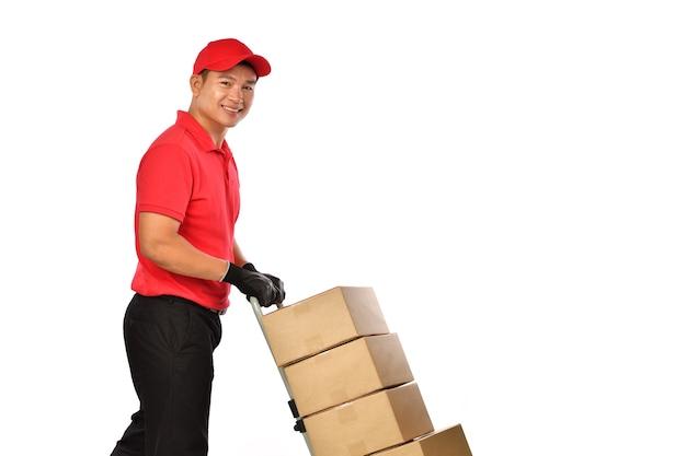 隔離されたボックスでハンドトラックを押す赤い制服を着た幸せな若いアジアの配達人。配達人が小包を発送します。