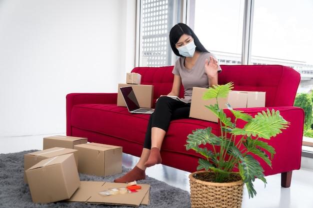 マスクの上の幸せな若いアジアの起業家は、顧客に製品を配信するためのボックスを配置しています