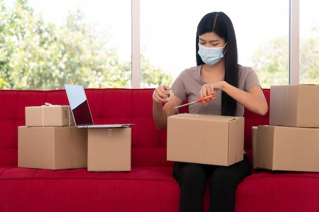 Счастливые молодые азиатские предприниматели в маске упаковывают коробки для доставки продуктов покупателям