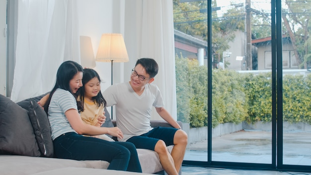 Happy young asian family play together on couch at home. chinese mother father and child daughter enjoying happy relax spending time together in modern living room in evening.
