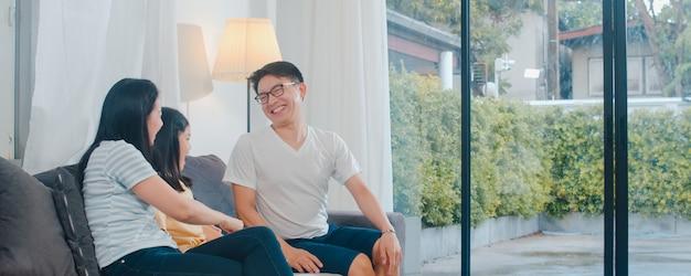 幸せな若いアジア家族が自宅のソファで一緒に遊ぶ。幸せを楽しんでいる中国の母父と子の娘は、夜にモダンなリビングルームで一緒に時間を過ごしてリラックスします。