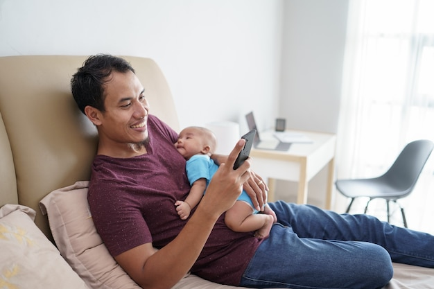Happy young asian father holding his newborn sweet adorable baby sleeping on his arms while using mobile phone on the bed