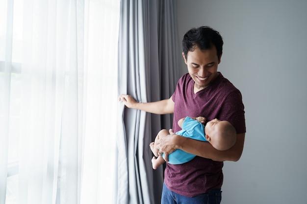 家にいる間彼の腕で眠っている彼の生まれたばかりの甘い愛らしい赤ちゃんを保持している幸せな若いアジアの父