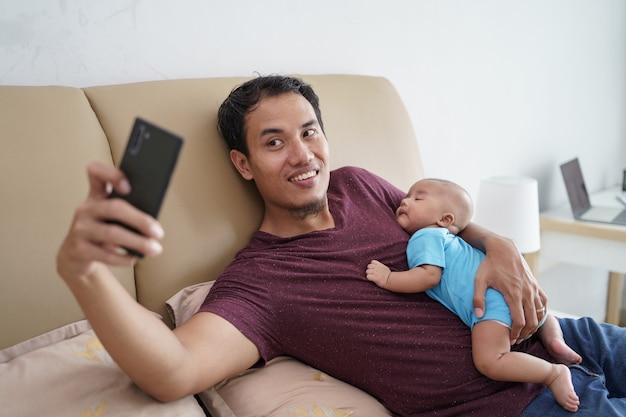 Счастливый молодой азиатский отец держит своего новорожденного сладкого очаровательного ребенка, спящего на его руках, используя мобильный телефон на кровати