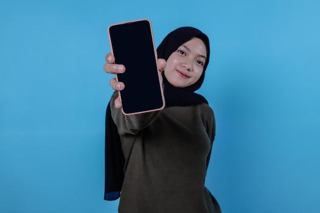 휴대 전화를 들고 빨간 긴 티셔츠를 입고 행복 한 젊은 아시아 여성