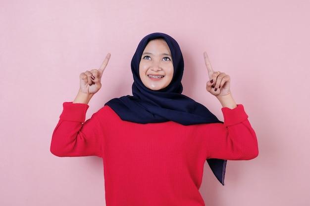 人差し指を作る赤い長いtシャツを着て幸せな若いアジアの女性