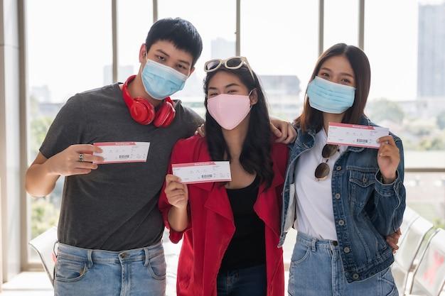 フェイスマスクを持った幸せな若いアジア人の友人が空港ターミナルで搭乗券を見せます。彼らは休暇休暇メーカーを取るために出発を待ちます。