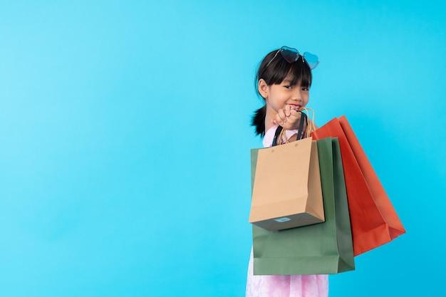 幸せな若いアジアの女の子子供スタイリッシュな持株ショッピングバッグ、子供のファッションスタイルコンセプトの有料のライフスタイル