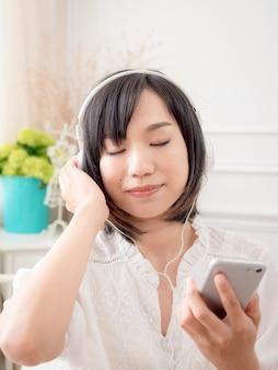 침대에서 음악을 듣고 행복 한 젊은 아시아 여자